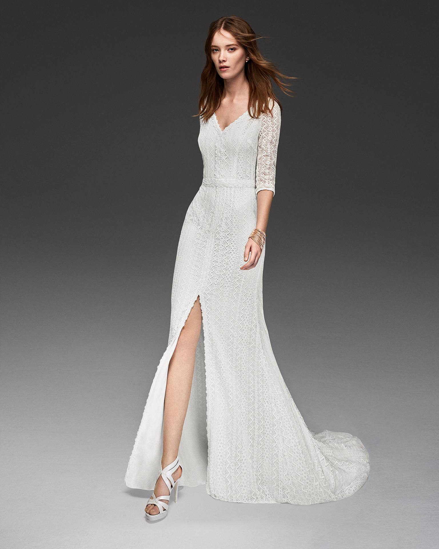 Boho-style beaded lace wedding dress with three-quarter sleeves and front opening.