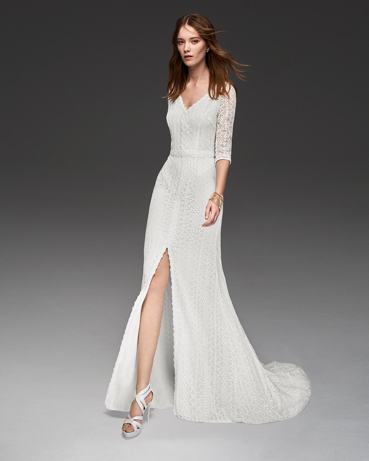 Vestido de novia estilo boho de encaje y pedreria de manga francesa con abertura delantera.