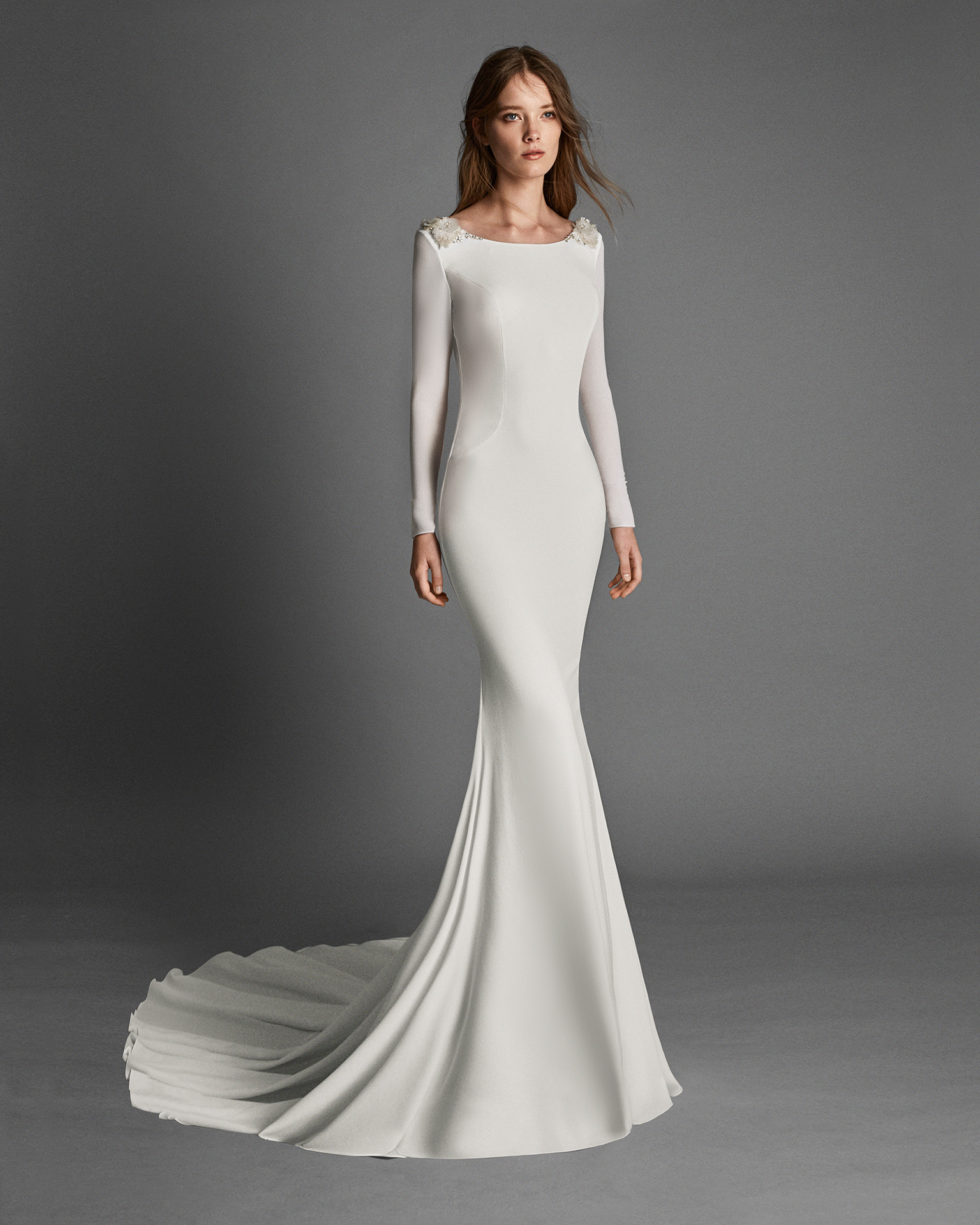 Mermaid-style crepe Georgette wedding dress with long sleeves, bateau neckline and crystal flowers on back.