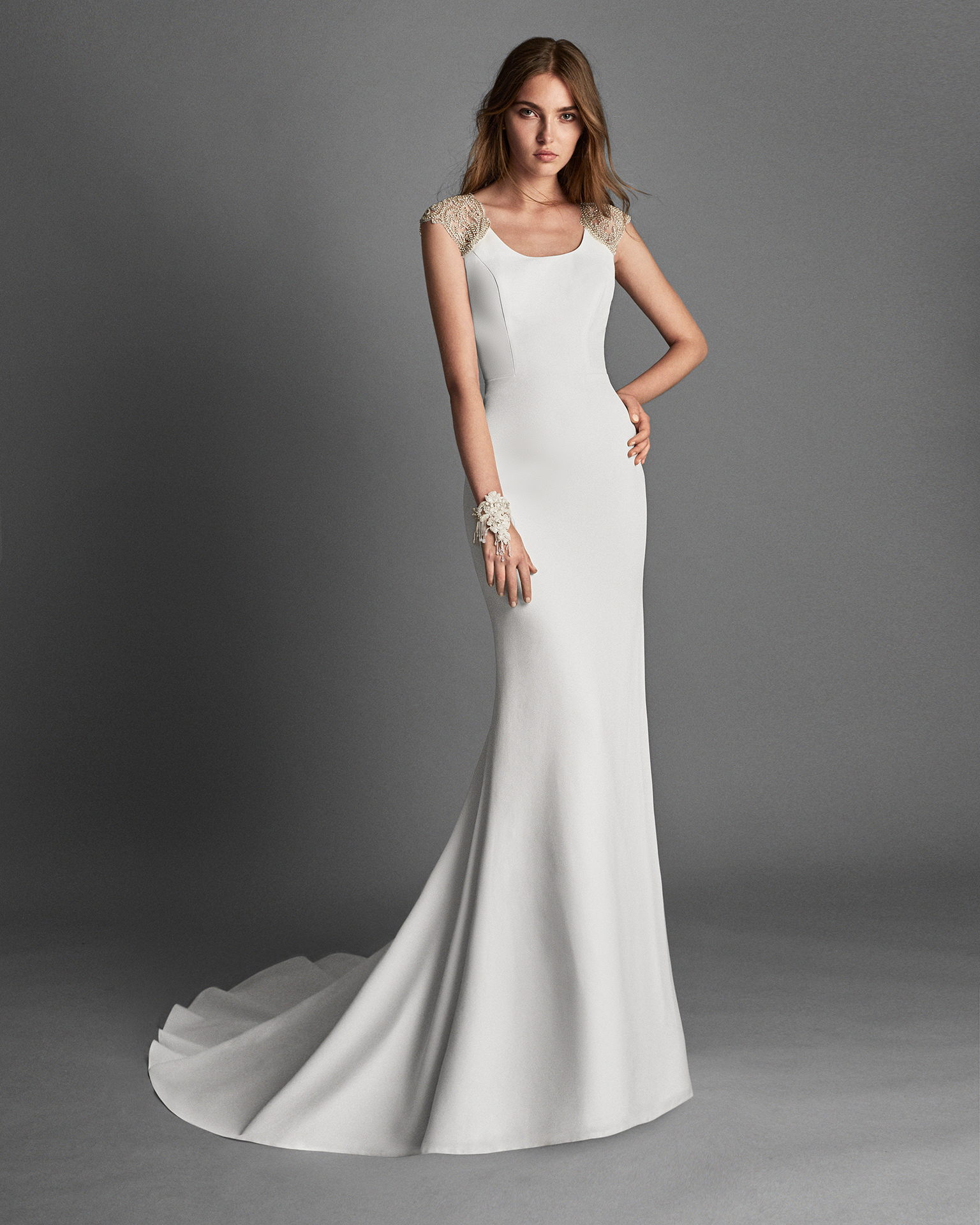 Mermaid-style crepe wedding dress with short sleeves and beaded lace back.