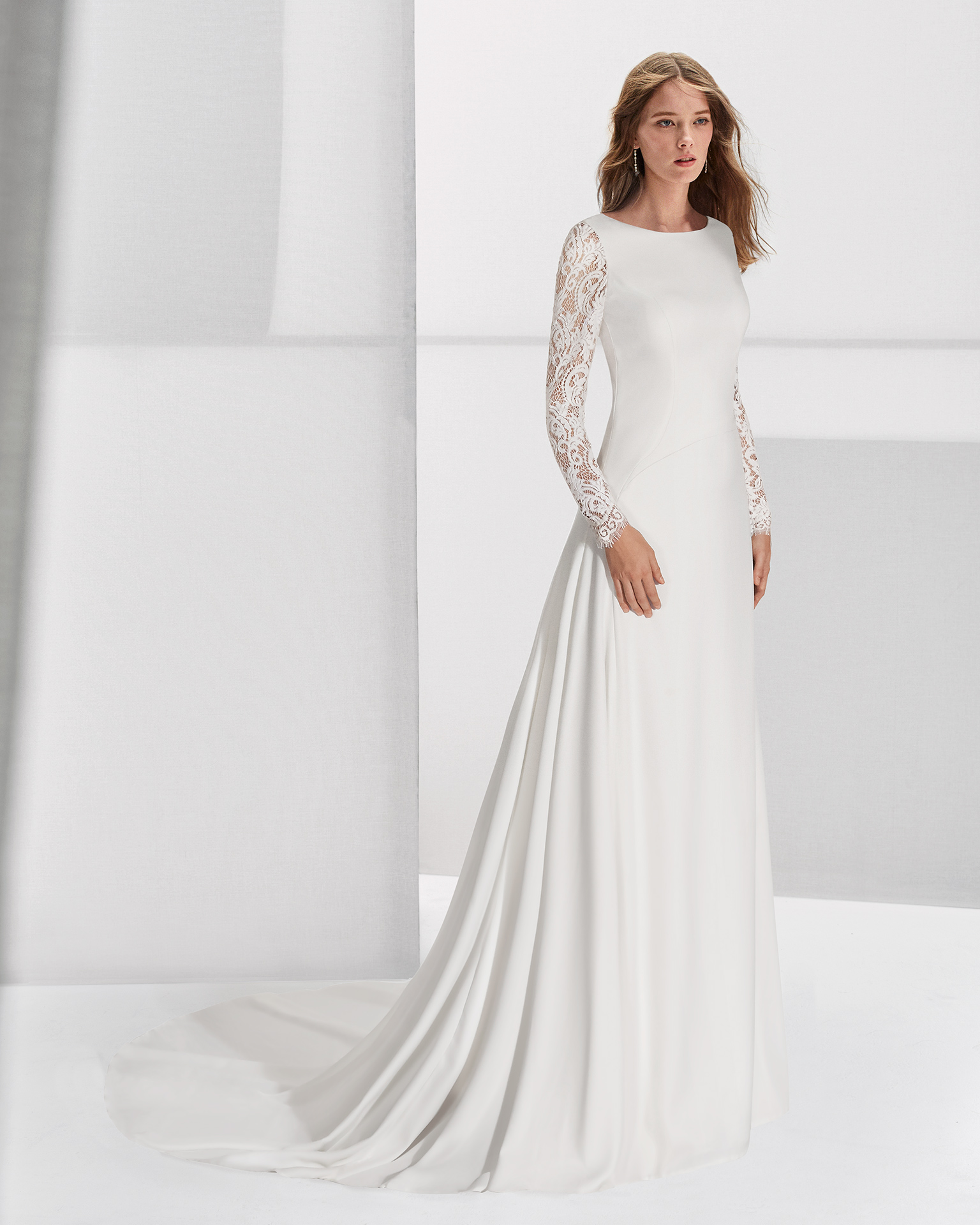 Crepe and lace sheath wedding dress with long sleeves, bateau neckline and low back.