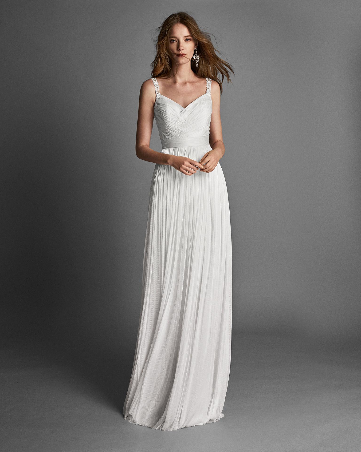 Vestido de novia corte recto de mouselina y espalda joya con adorno de pedrería.