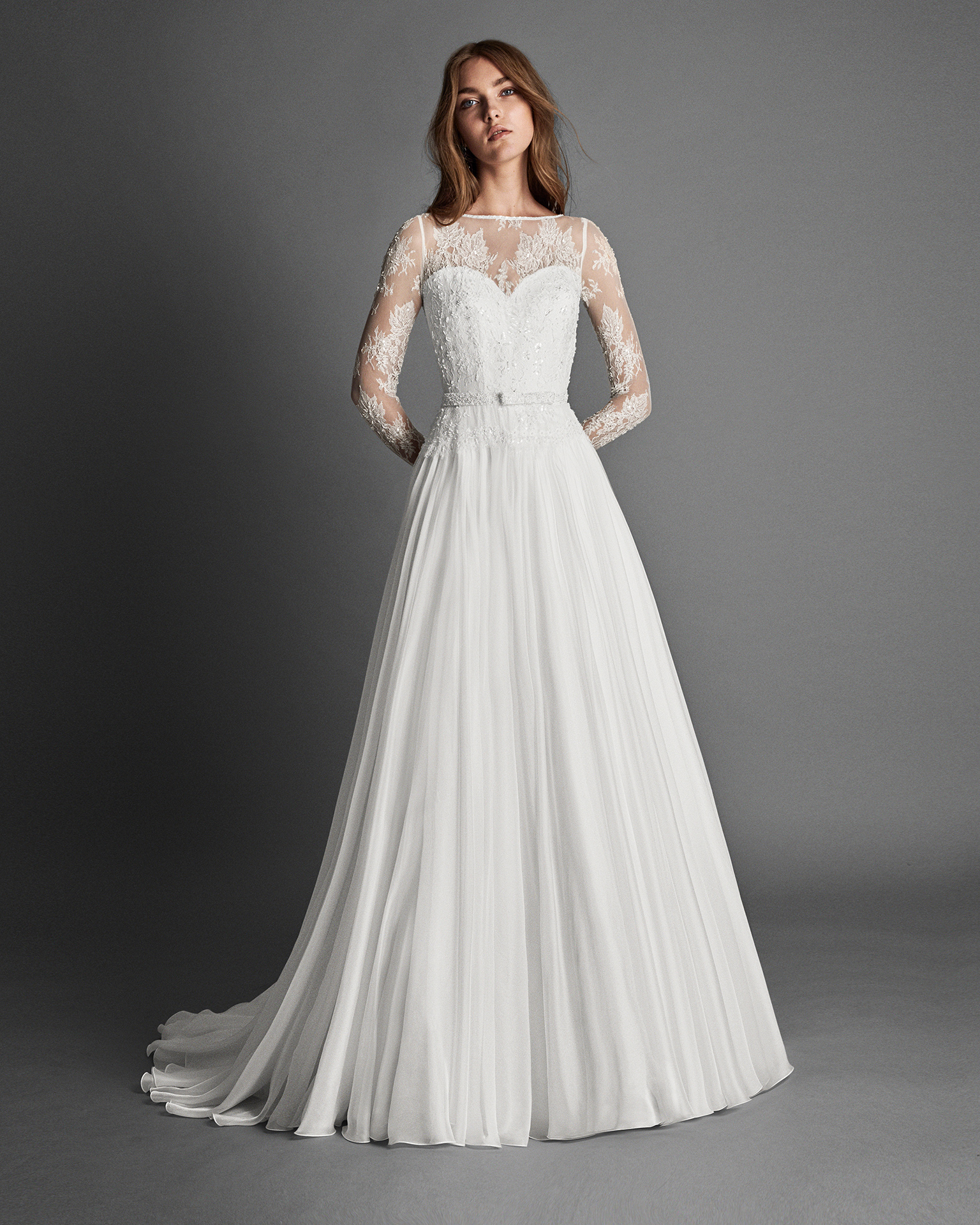 A-line voile and lace wedding dress with long sleeves, and low back with beadwork detail.