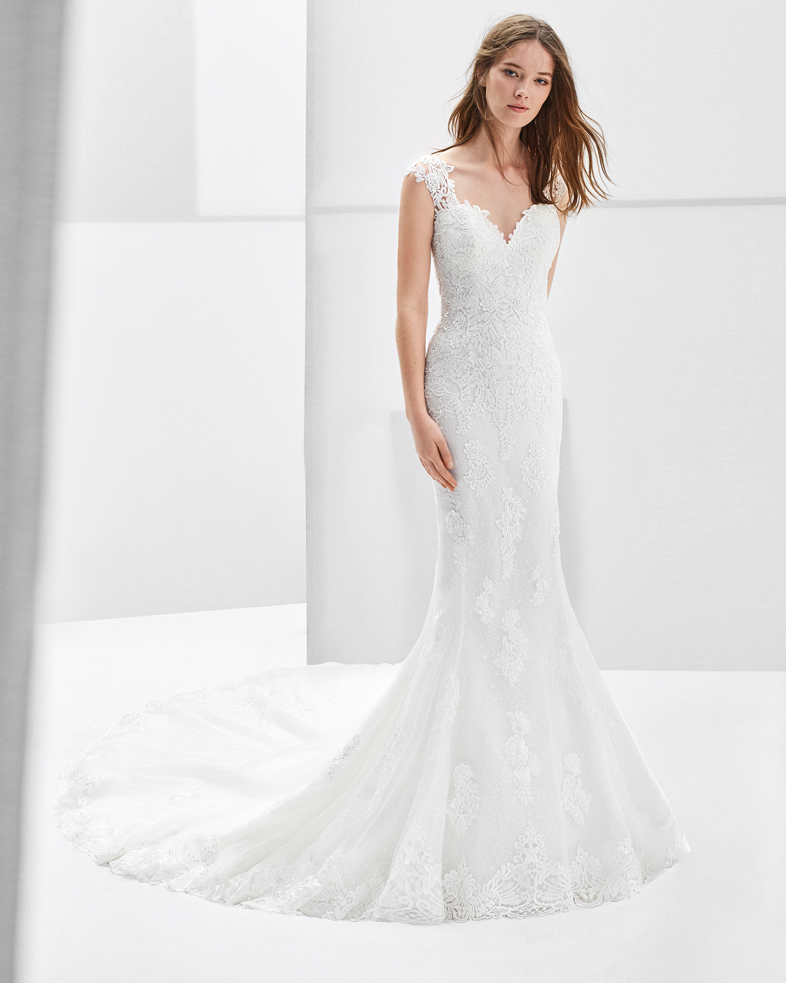 Mermaid-style lace and guipure lace wedding dress with low back and lace appliqués.