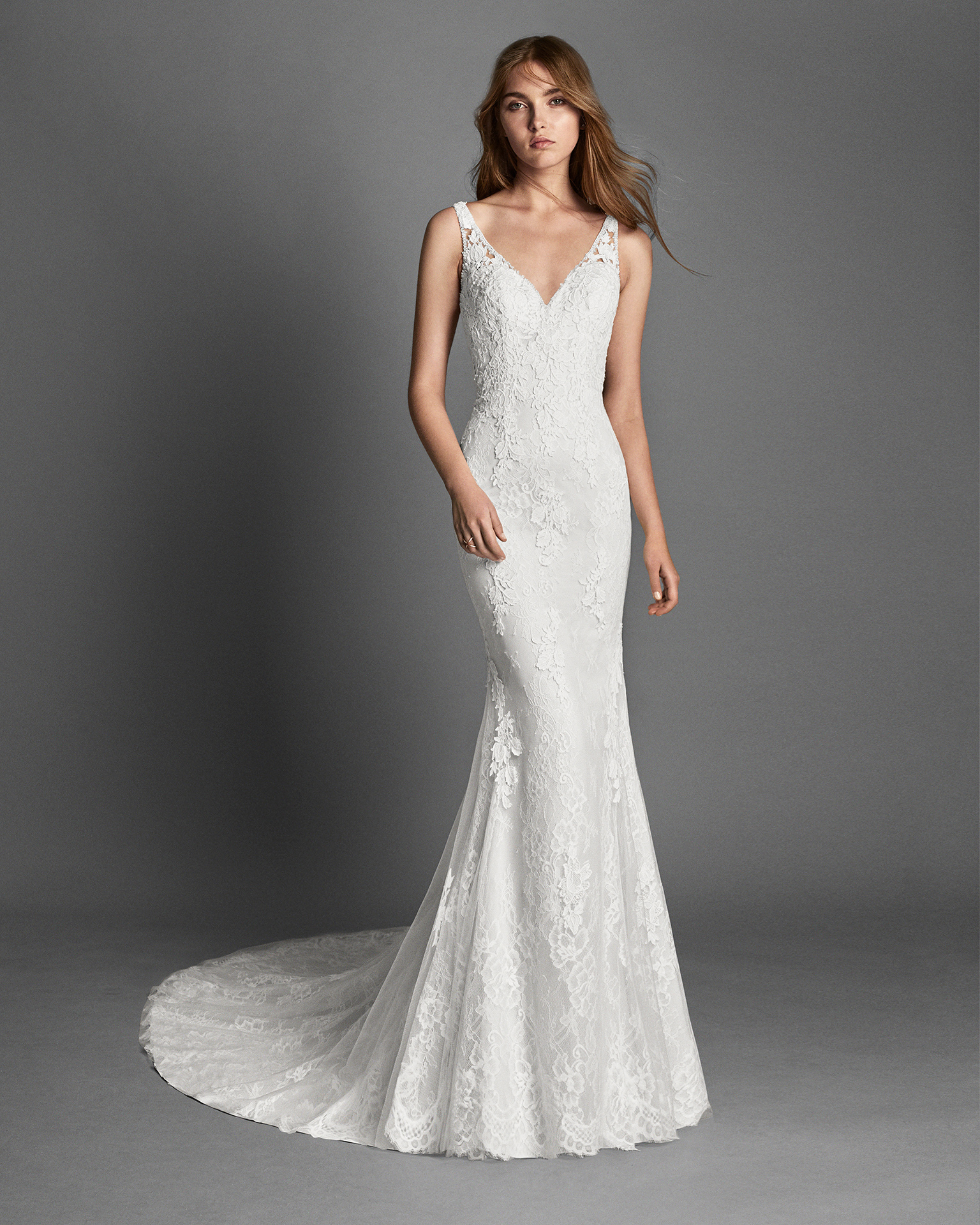 Mermaid-style beaded lace and guipure lace wedding dress with low back and lace appliqués.
