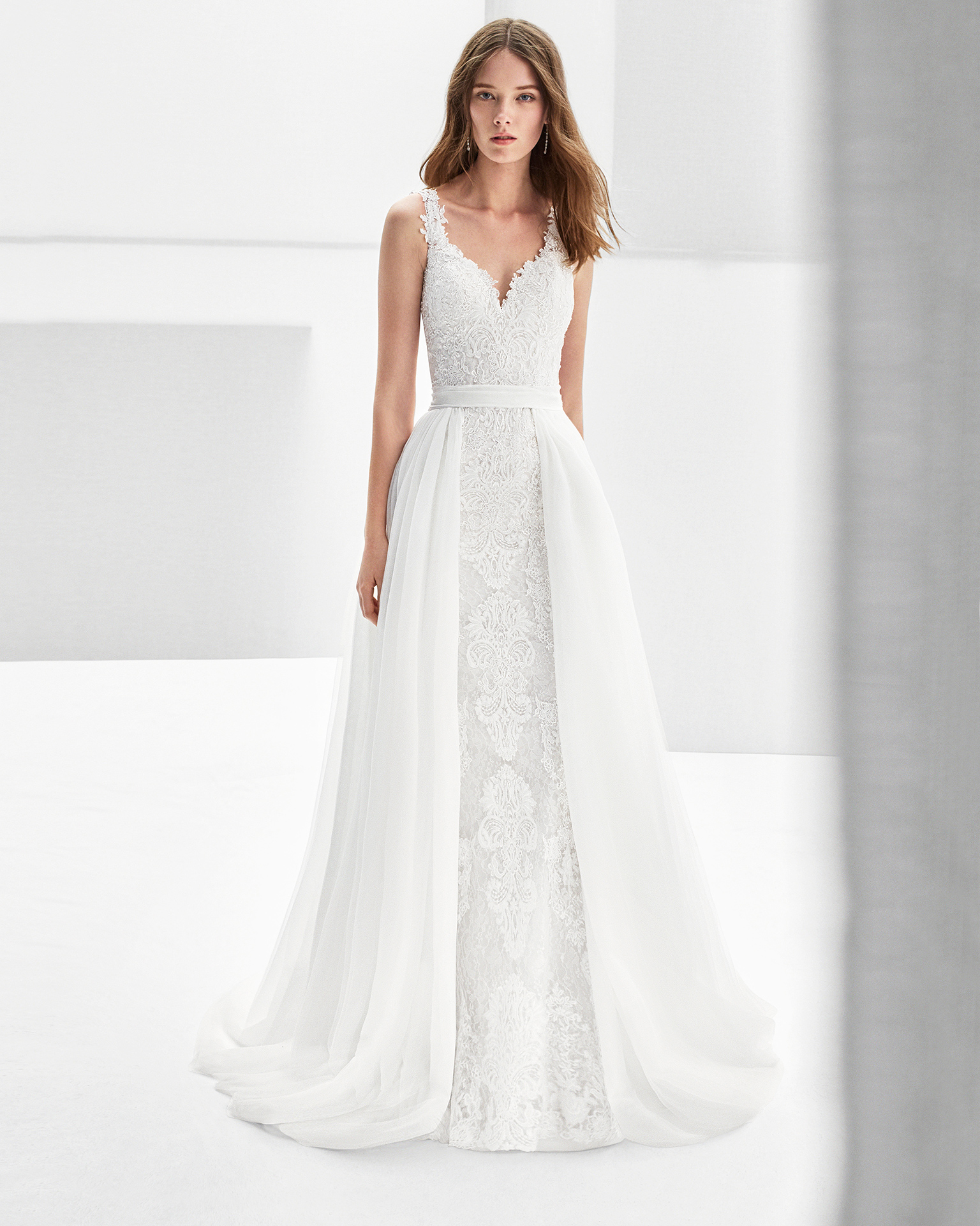 Mermaid-style guipure lace wedding dress with low back and overskirt.