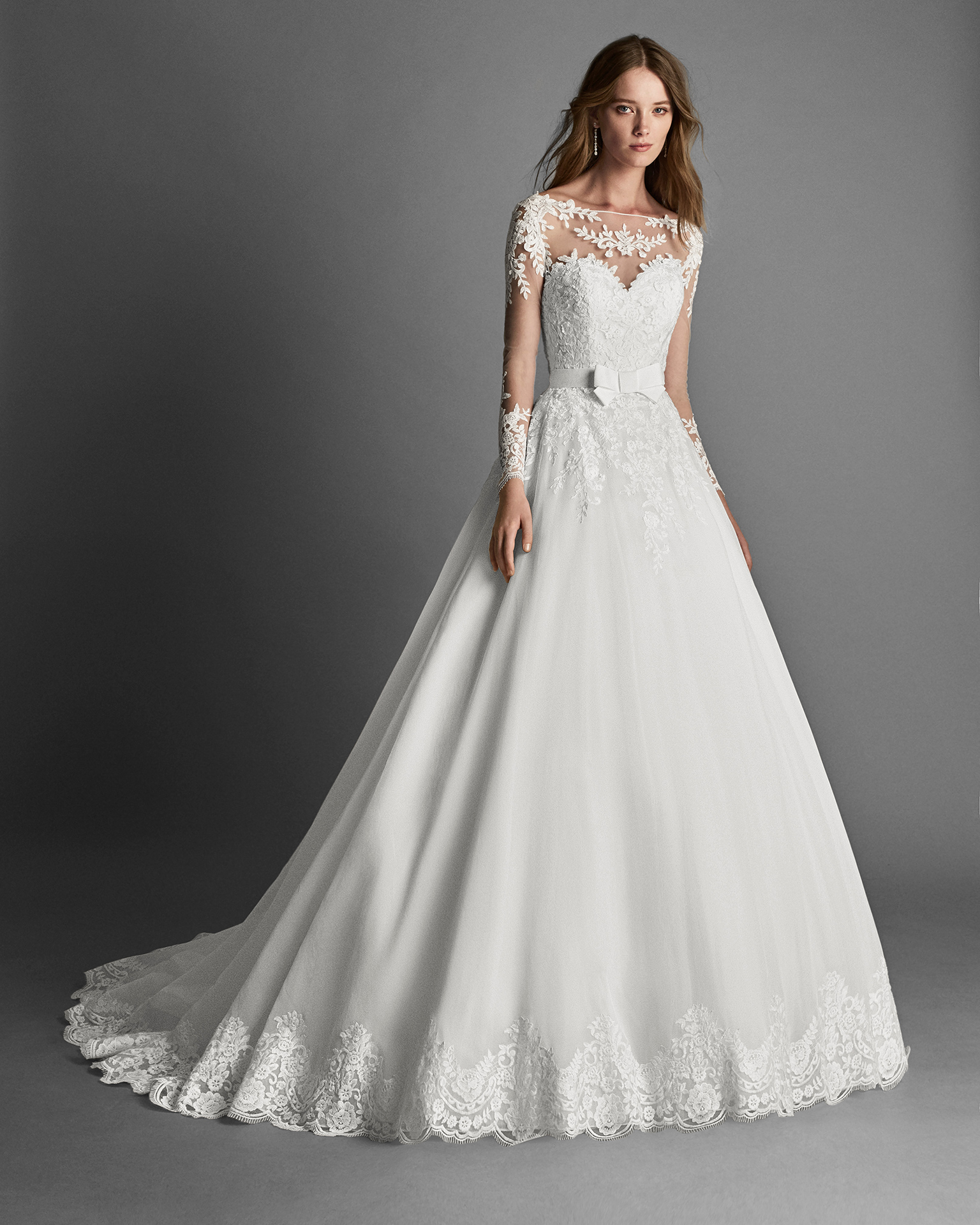 Princess-style garza and lace wedding dress with long sleeves and lace appliqués.