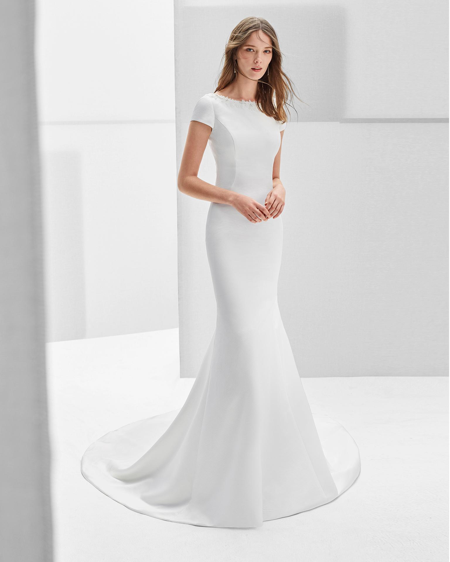 Vestido de novia estilo clásico en ottoman y pedreria con escote barco. Espalda escotada con adorno de pedrería en color natural.