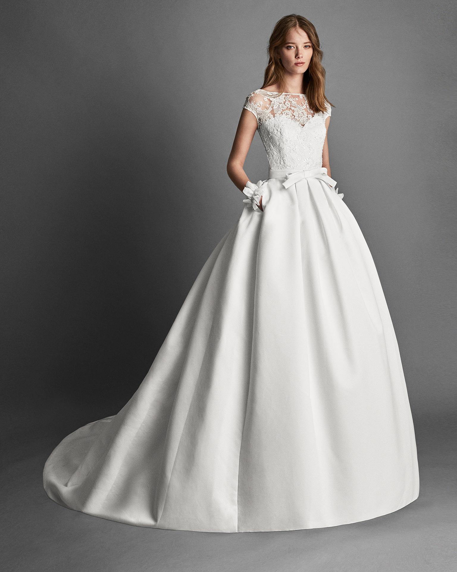Vestido de novia estilo clásico de ottoman y encaje pedrería de manga corta. Escote barco con bolsillos en color marfil.