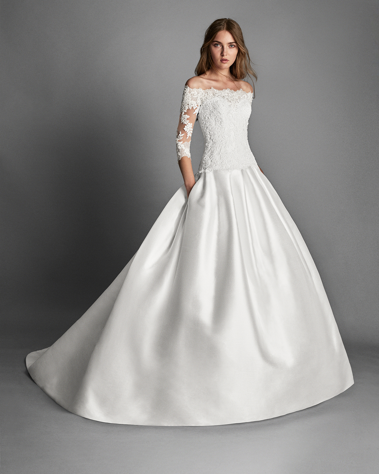 Classic-style beaded lace and mikado wedding dress with long sleeves and pockets, in natural.