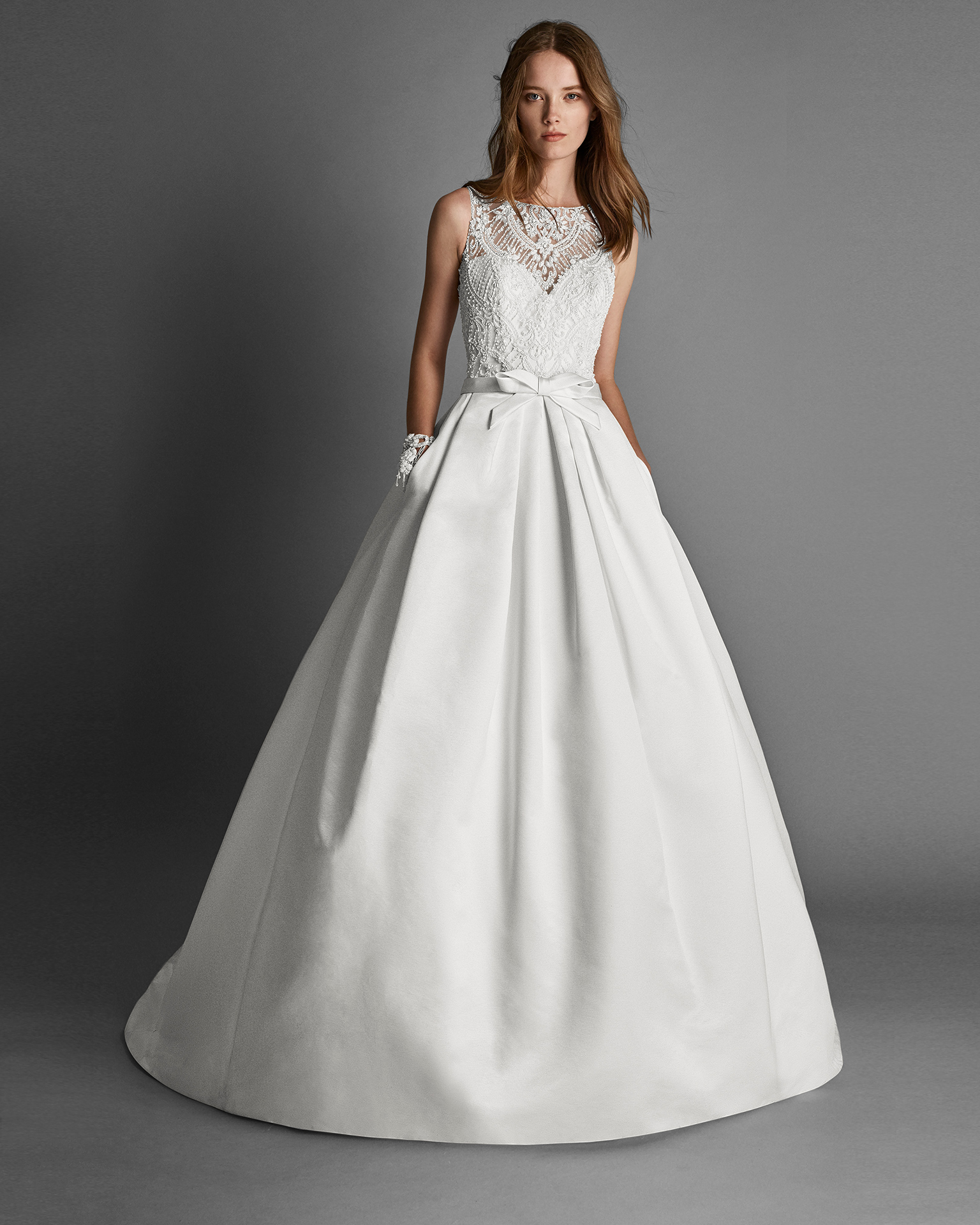 Classic-style beaded lace and duchess satin wedding dress with halter neckline, beaded embroidery back and pockets, in ivory.