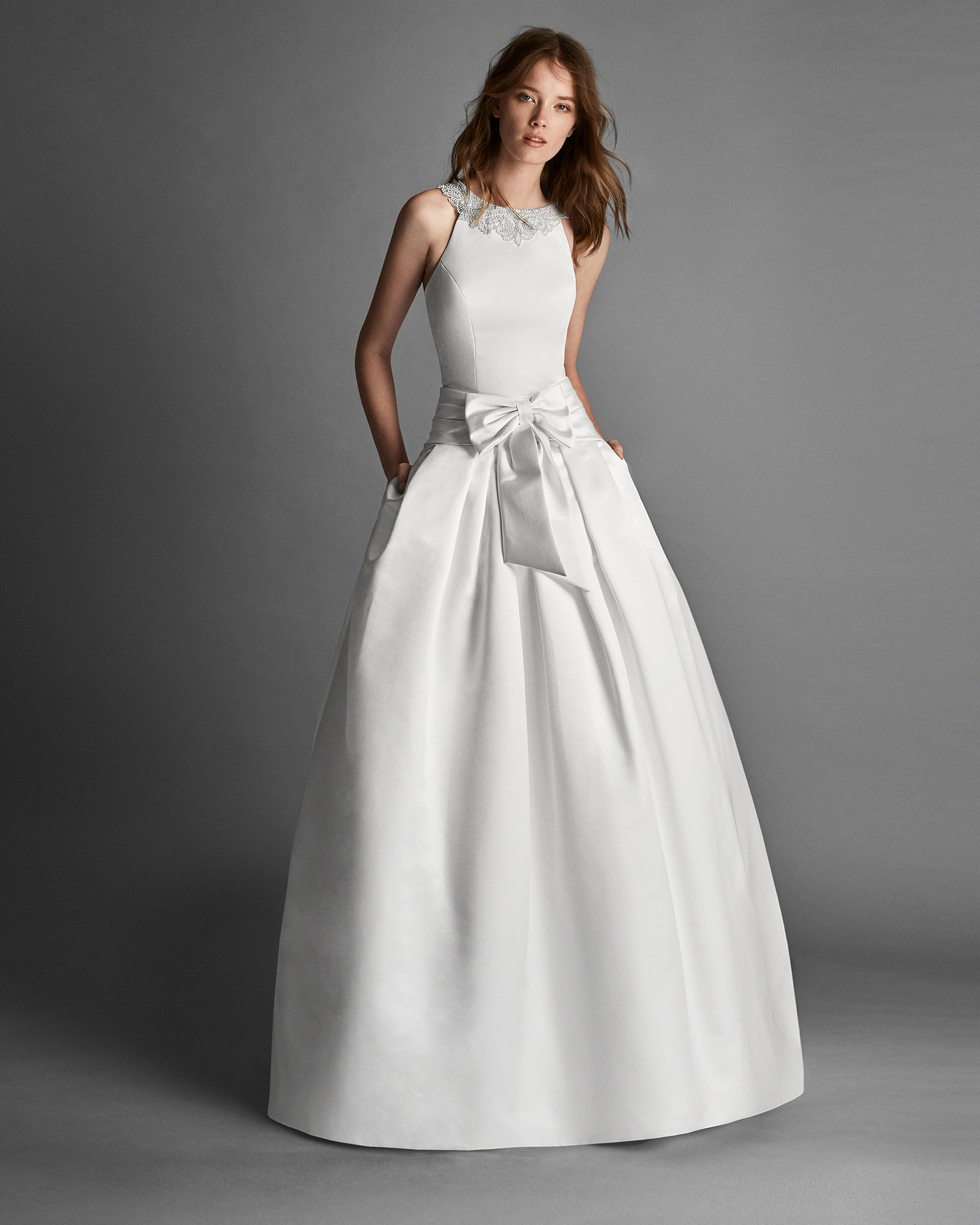 Classic-style beaded duchess satin wedding dress with low back and pockets, in ivory.