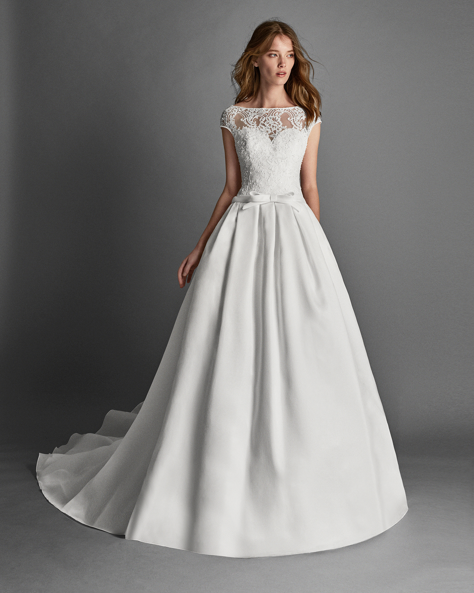 Classic-style beaded lace and organza wedding dress with short sleeves and low back.