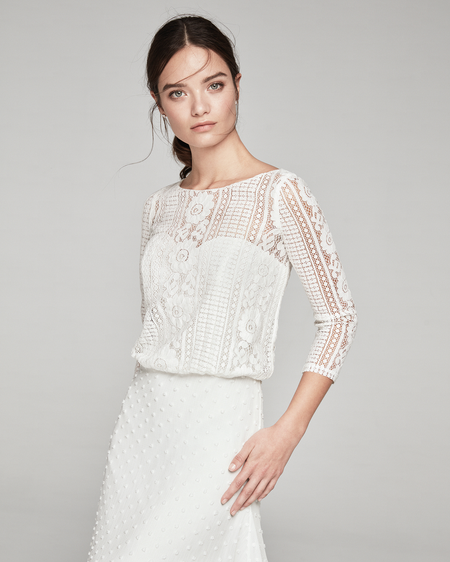 Boho-style wedding dress in lace. Bateau neckline with three-quarter sleeves and polka-dot gauze skirt. Available in natural. 2019 ALMA_NOVIA Collection.