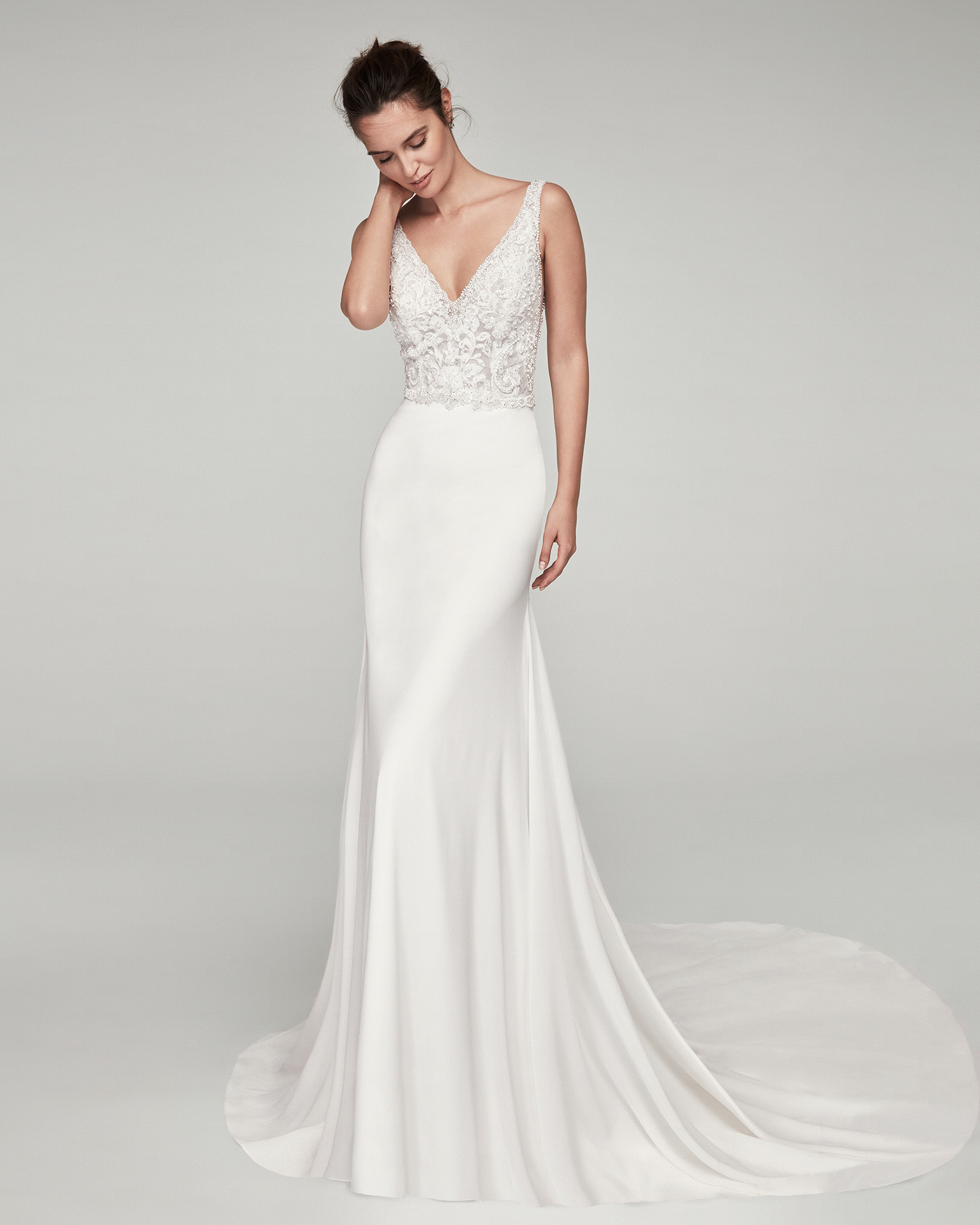 Sheath-style wedding dress in crepe Georgette and beaded lace. With V-neckline and back. Available in natural. 2019 ALMA_NOVIA Collection.