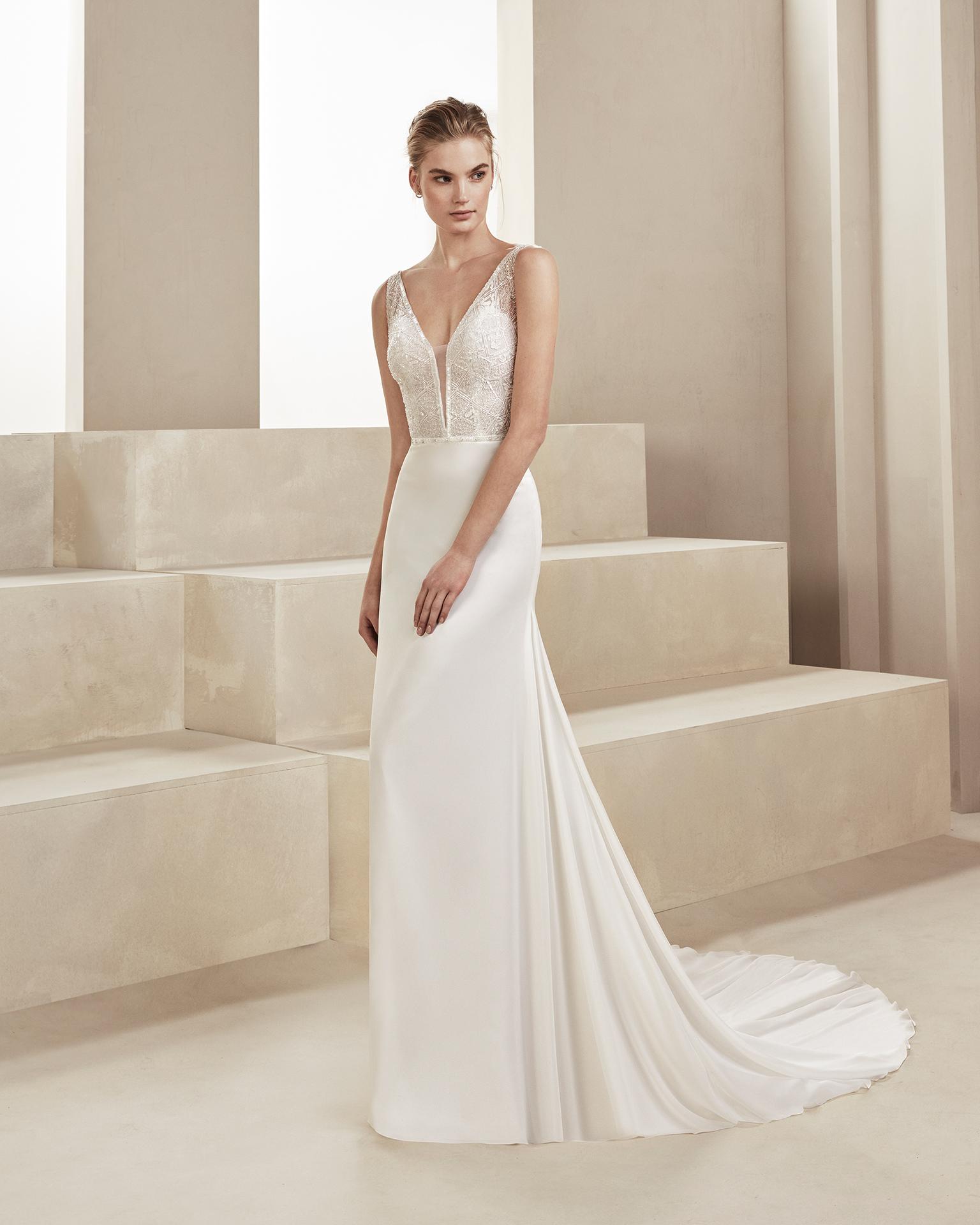 Vestido de novia corte recto en gasa y pedrería. Con escote deep-plunge y espalda en V. Disponible en color natural. Colección ALMANOVIA 2019.