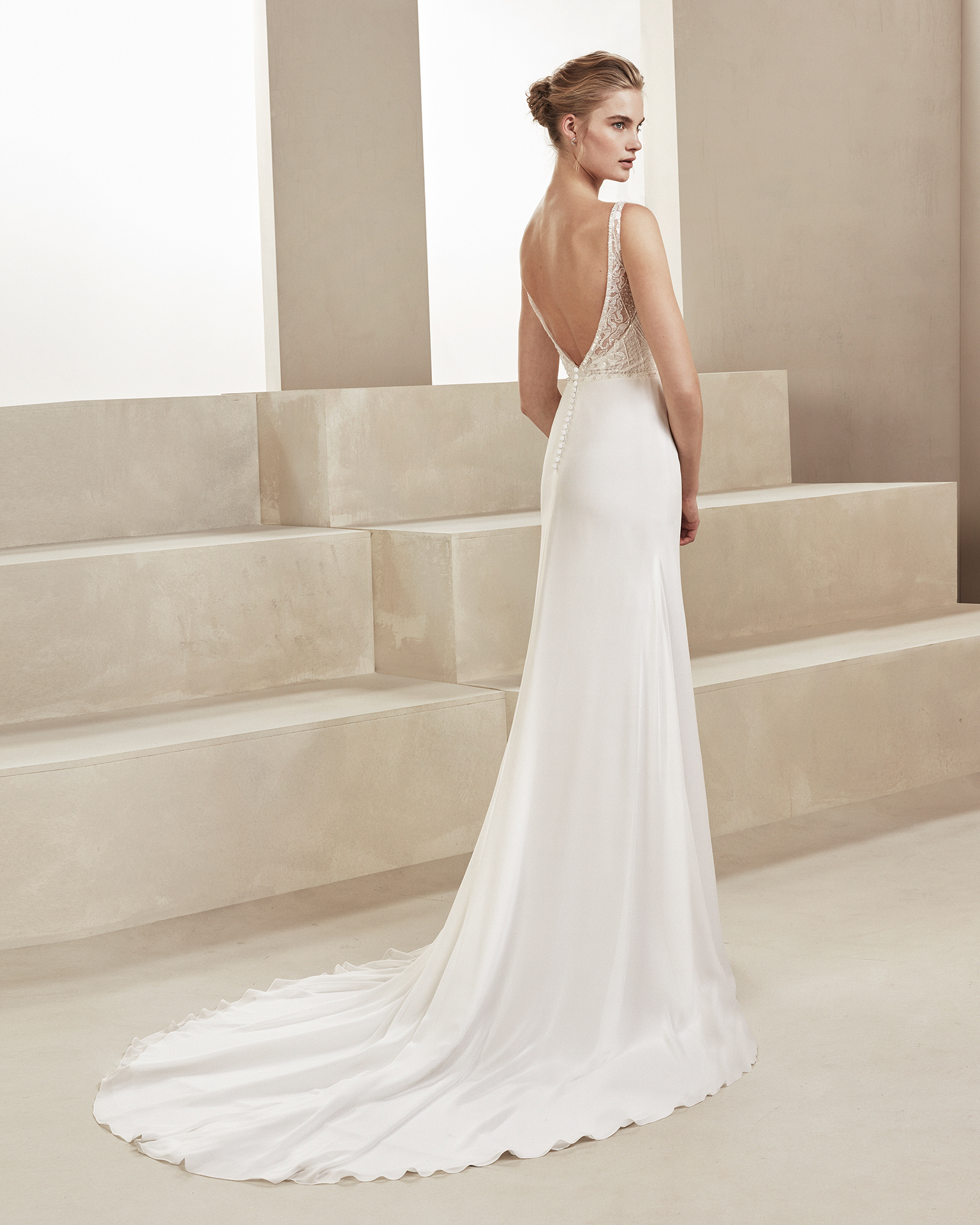 Sheath-style wedding dress in beaded chiffon. With deep-plunge neckline and V-back. Available in natural. 2019 ALMA_NOVIA Collection.
