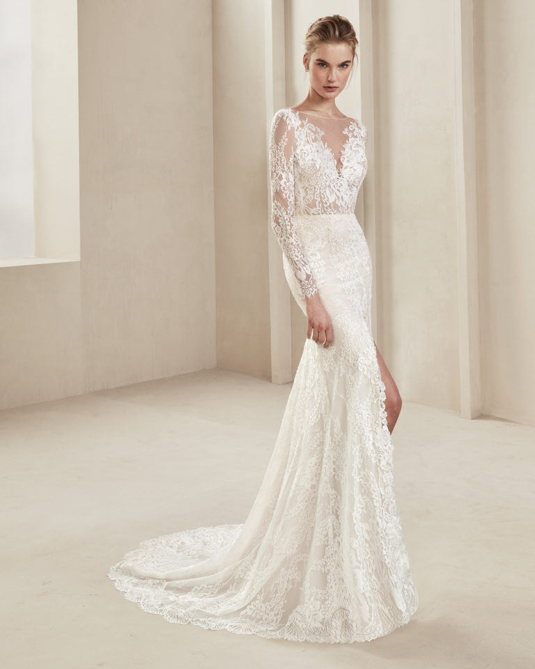 Sheath-style lace wedding dress. With deep-plunge neckline and long sleeves. Skirt with front slit. Available in natural/nude and natural. 2019 ALMA_NOVIA Collection.