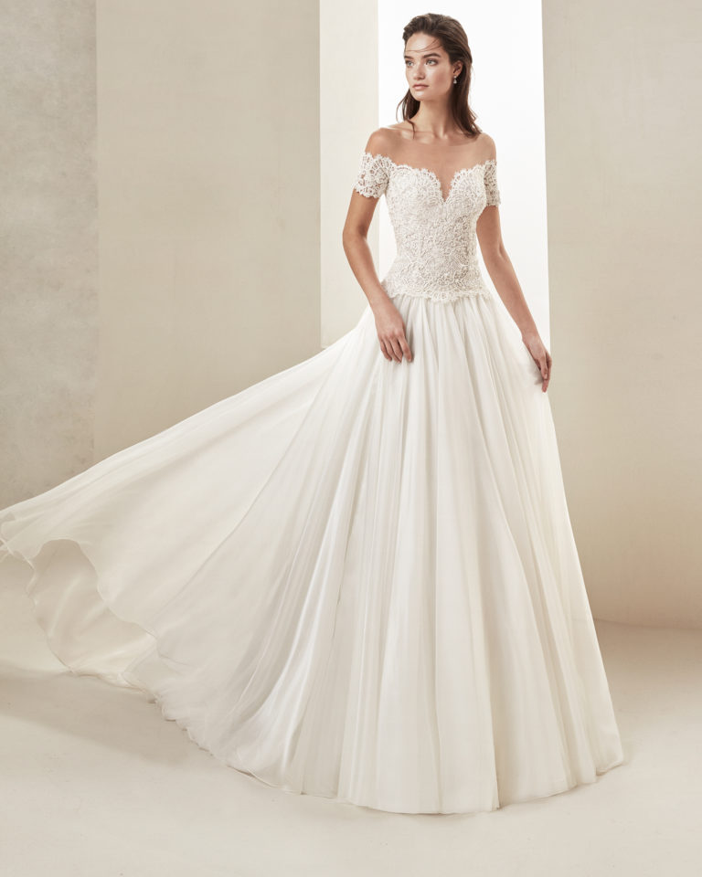 Romantic wedding dress in voile and beaded lace. With sweetheart neckline and off-the-shoulder sleeves. Available in natural. 2019 ALMA_NOVIA Collection.