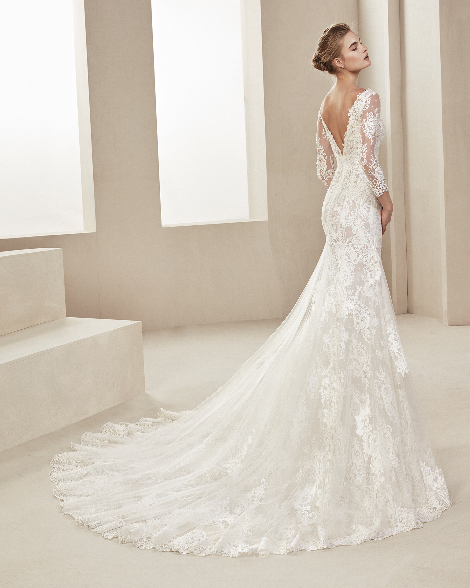 Mermaid-style lace wedding dress. With V-neckline, low back and long sleeves. Available in natural. 2019 ALMA_NOVIA Collection.
