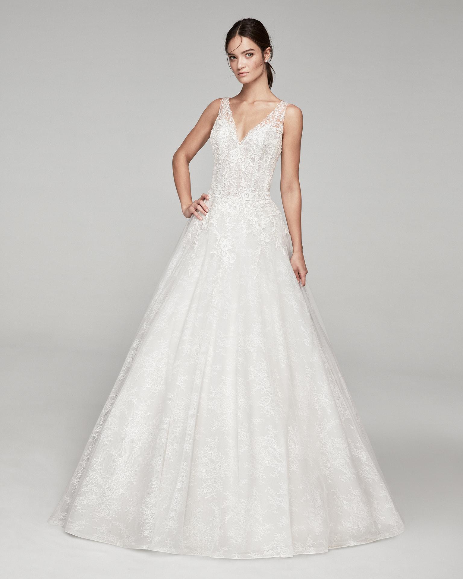 Vestido de novia romántico de encaje. Con escote V en       pedrería y espalda de tul. Disponible en color hielo y      natural. Colección ALMANOVIA 2019.