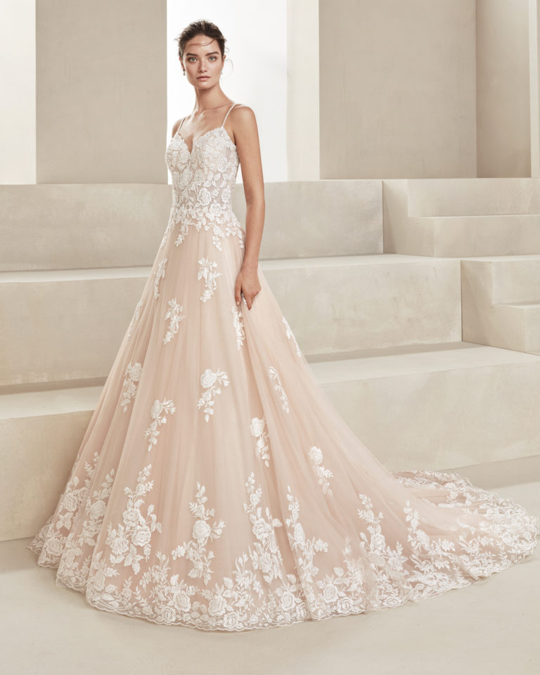 Romantic wedding dress in tulle and beaded lace. With sweetheart neckline and beaded straps. Skirt with lace appliqués. Available in ice, amber and natural. 2019 ALMA_NOVIA Collection.