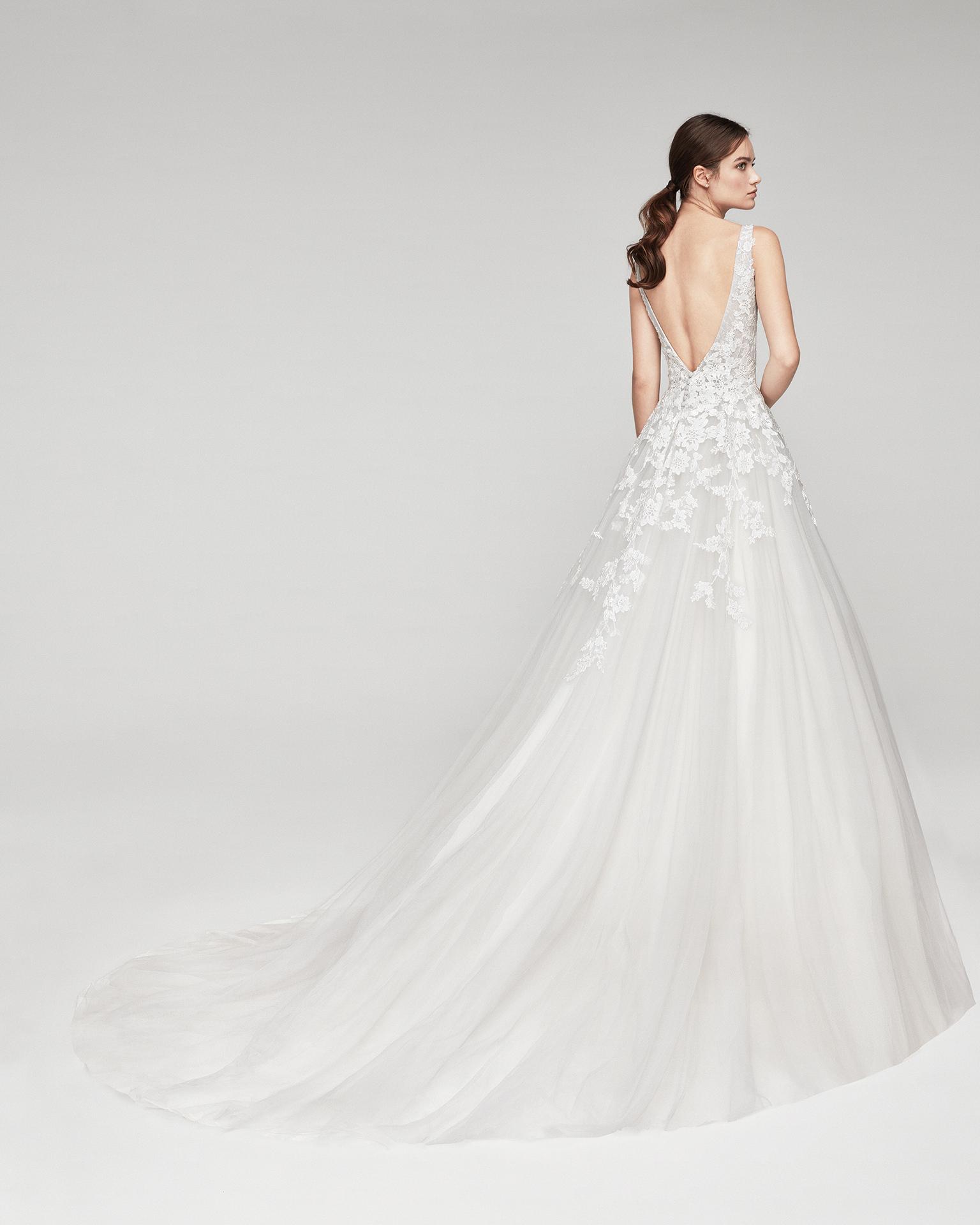 Vestido de novia romántico de tul y encaje. Con escote deep-plunge y espalda escotada en V. Disponible en color hielo y natural. Colección ALMANOVIA 2019.