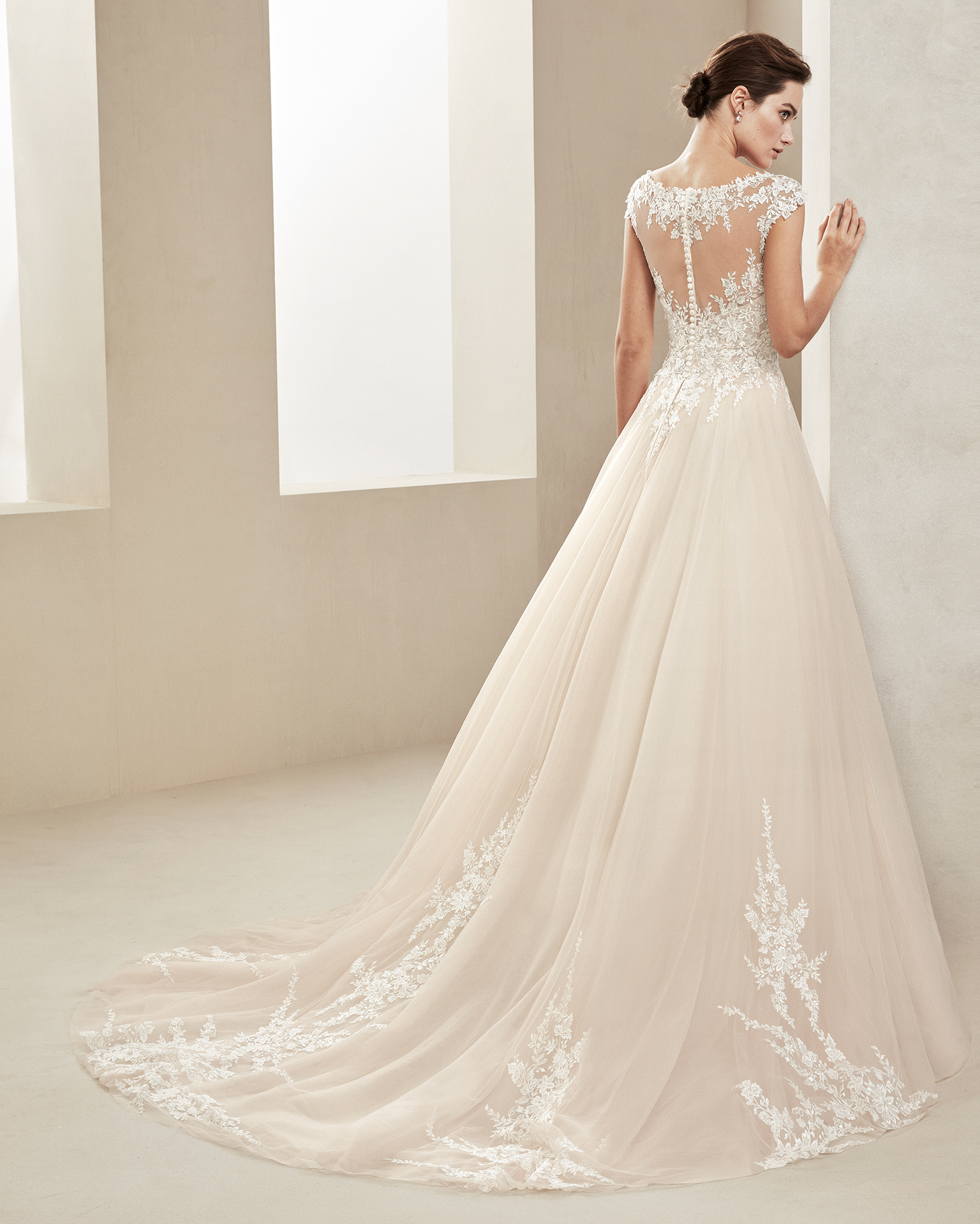 Romantic tulle and lace wedding dress. With V-neckline and tulle and lace back. Skirt with lace appliqués. Available in amber and natural. 2019 ALMA_NOVIA Collection.