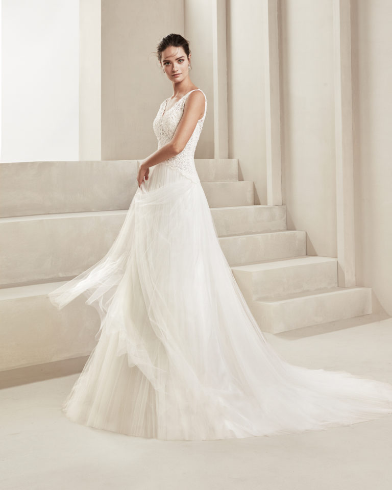 Romantic soft tulle and beaded lace wedding dress. With V-neckline and tulle back. Available in natural. 2019 ALMA_NOVIA Collection.