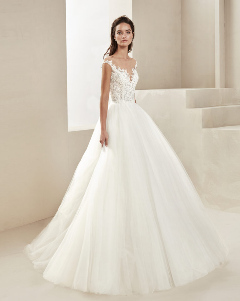 Romantic wedding dress in tulle and beaded lace. With illusion neckline and V-back. Available in ivory. 2019 ALMA_NOVIA Collection.