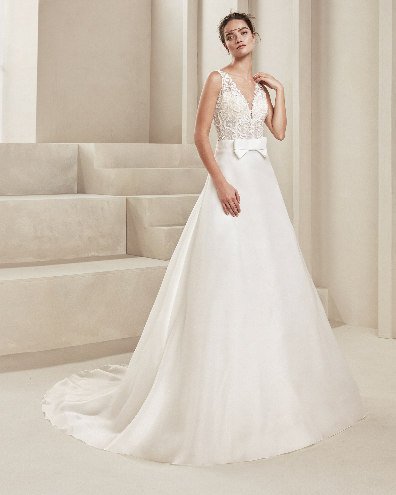 Classic wedding dress in organza and beaded lace. With deep-plunge neckline and teardrop back. With bow at the waist. Available in natural. 2019 ALMA_NOVIA Collection.