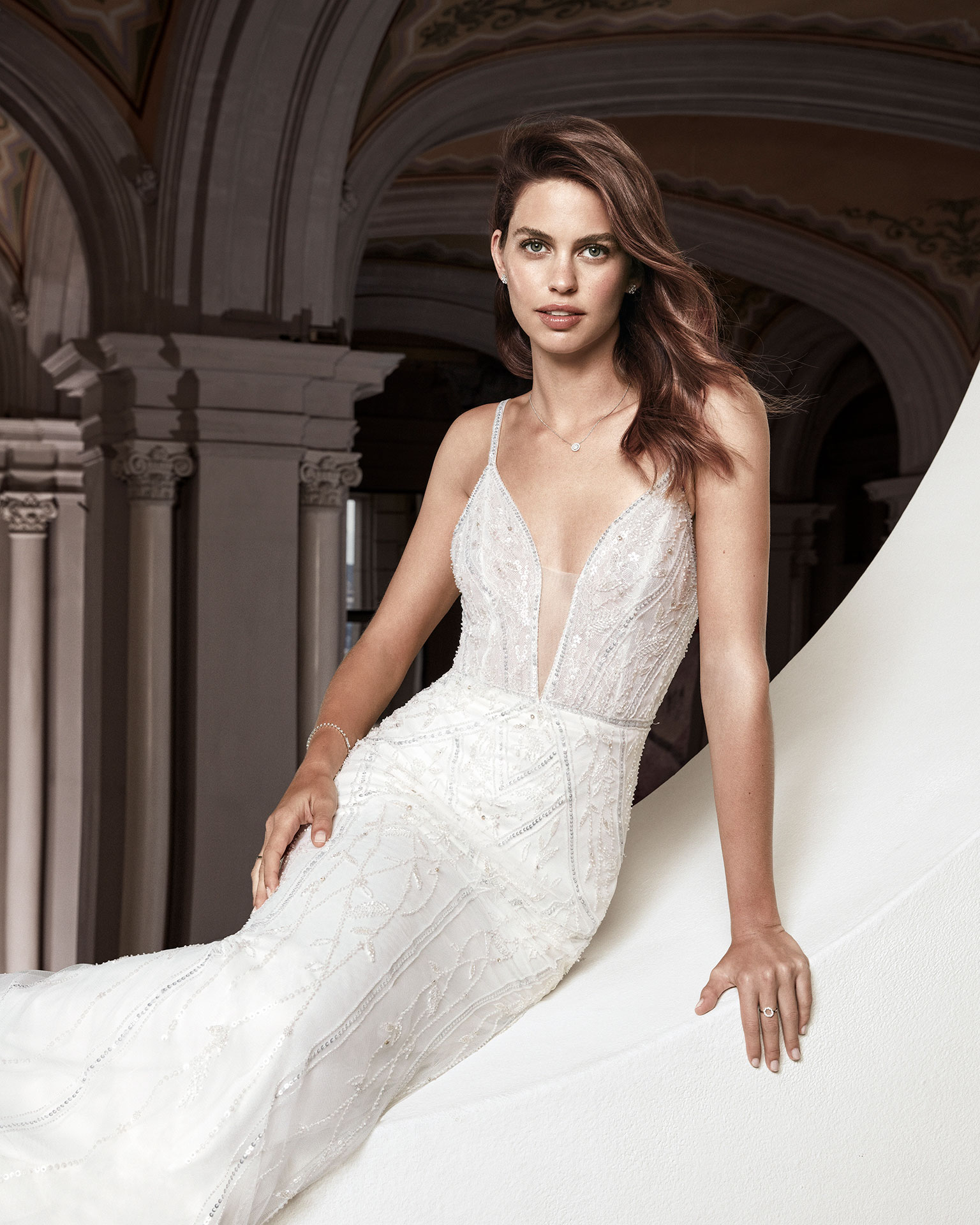 Beaded sheath-style wedding dress. Deep-plunge neckline and beaded straps with V-back. Available in natural. 2019 ALMA_NOVIA Collection.