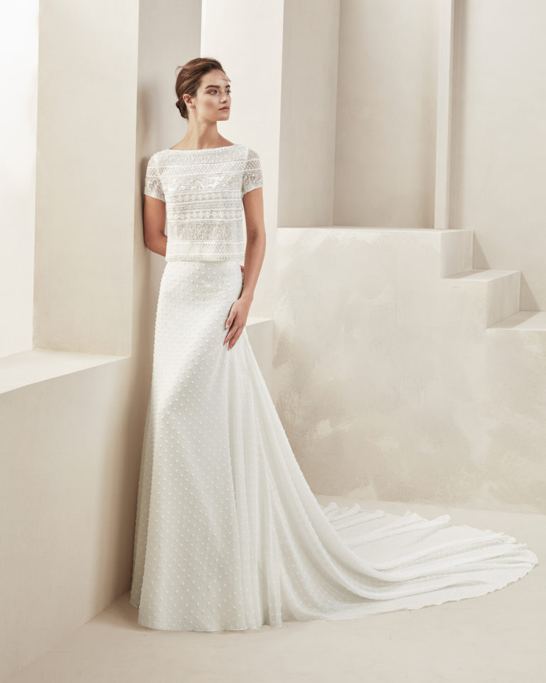 Two-piece boho-style wedding dress. With beaded lace bodice. Bateau neckline, short sleeves and plain polka-dot gauze skirt. Available in natural. 2019 ALMA_NOVIA Collection.