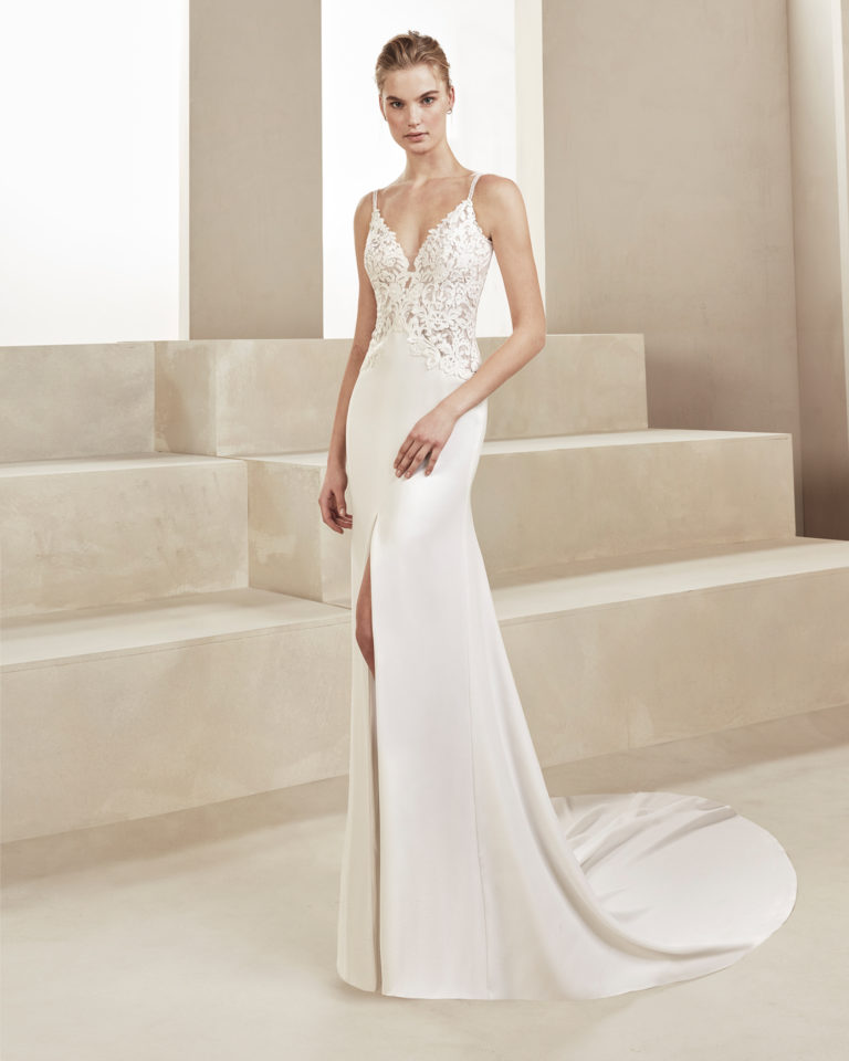 Sheath-style wedding dress in crepe and lace. With deep-plunge neckline and beaded straps. Available in natural. 2019 ALMA_NOVIA Collection.