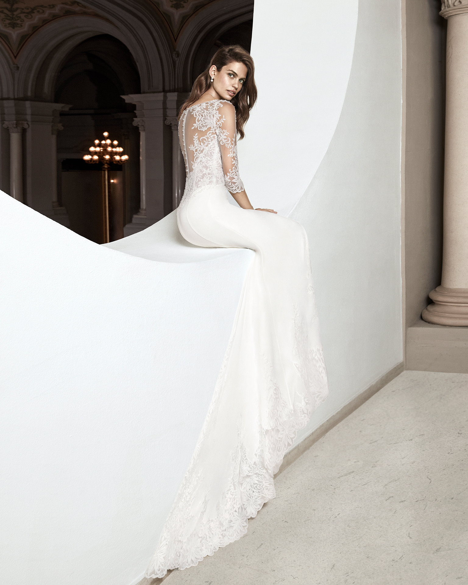 Sheath-style wedding dress in crepe Georgette and beaded lace. With V-neckline and three-quarter sleeves in tulle and beaded lace. Available in natural. 2019 ALMA_NOVIA Collection.
