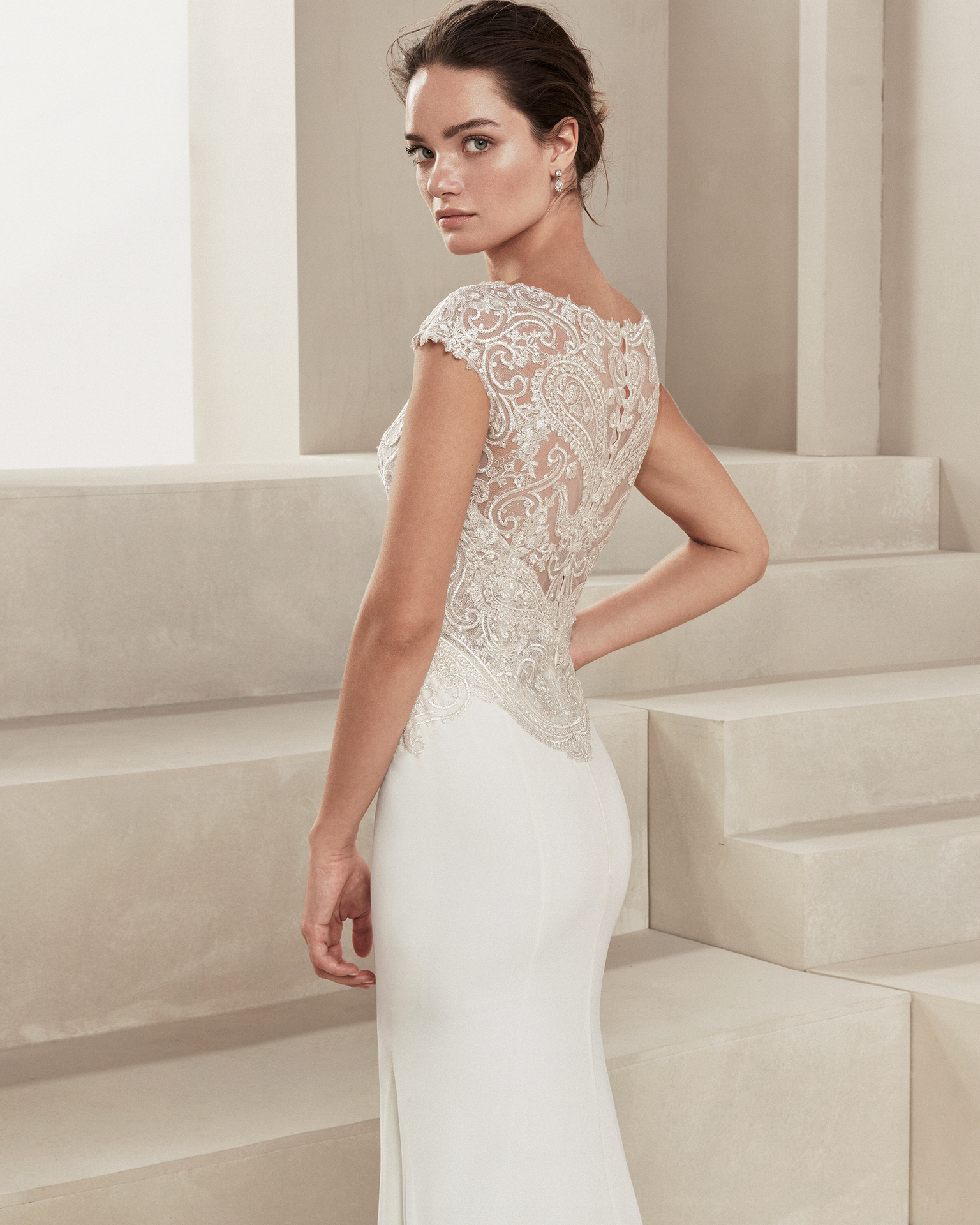 Sheath-style wedding dress in crepe Georgette and beaded lace. With V-neckline. Available in natural. 2019 ALMA_NOVIA Collection.