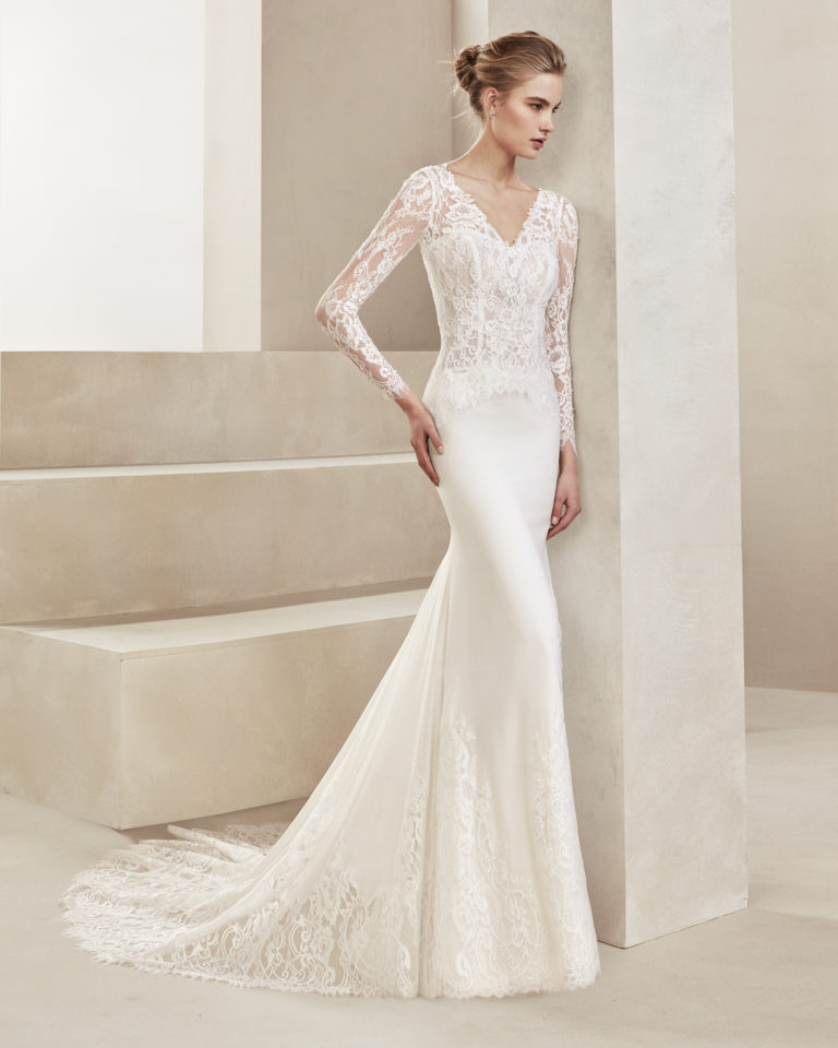 Sheath-style wedding dress in crepe Georgette and beaded lace. With V-neckline and long lace sleeves. Available in natural. 2019 ALMANOVIA Collection.
