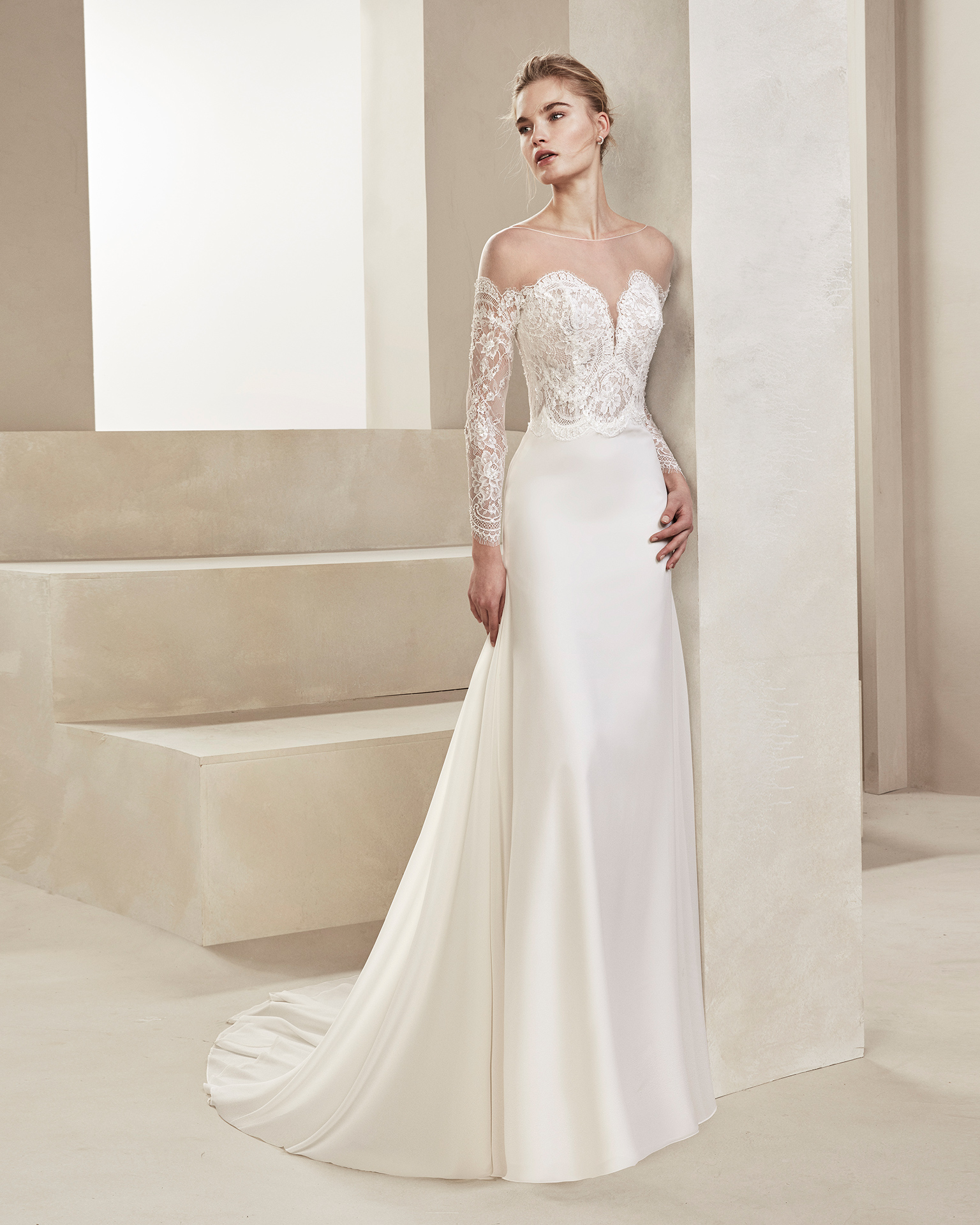 Sheath-style wedding dress in crepe Georgette and beaded lace. With sweetheart neckline and long lace sleeves. Available in natural. 2019 ALMA_NOVIA Collection.