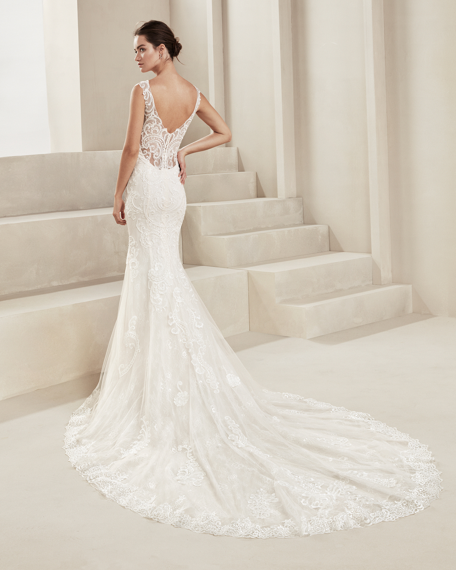 Mermaid-style beaded lace wedding dress. With V-neckline and low back. Available in natural. 2019 ALMA_NOVIA Collection.