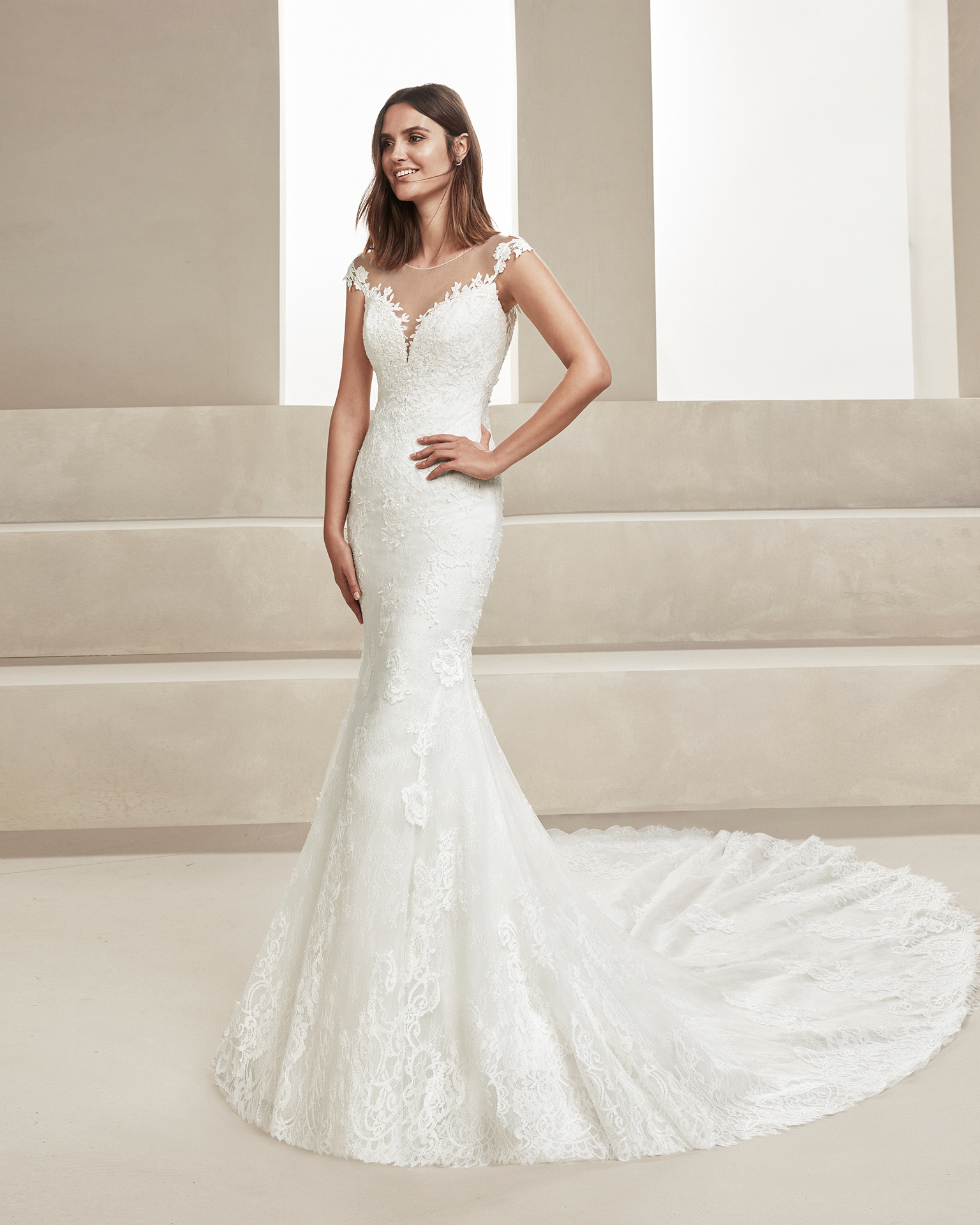 Mermaid-style beaded lace wedding dress. With illusion neckline and lace back. Available in natural. 2019 ALMA_NOVIA Collection.