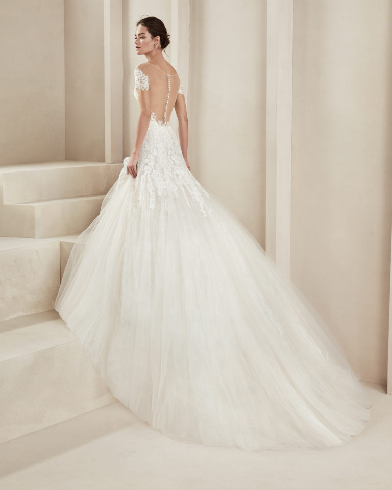 Romantic tulle and lace wedding dress. With sweetheart neckline, tulle back and off-the-shoulder sleeves. Available in natural. 2019 ALMA_NOVIA Collection.