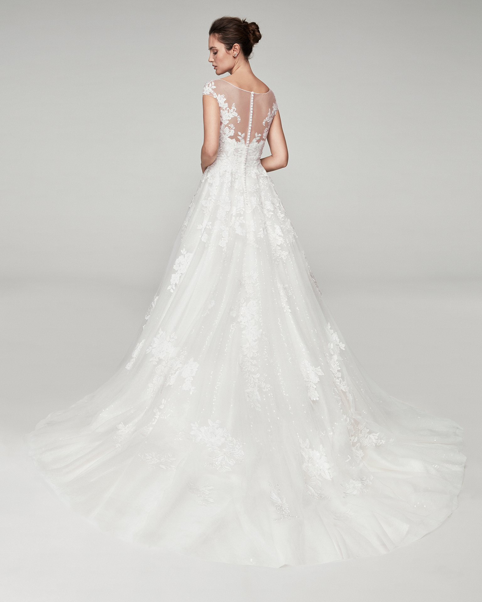 Romantic tulle and beaded lace wedding dress. With V-neckline and tulle back. Skirt with lace appliqués. Available in natural. 2019 ALMA_NOVIA Collection.