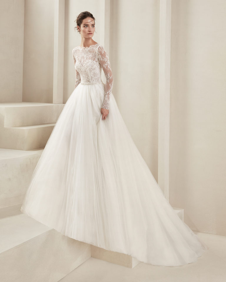 Romantic wedding dress in tulle and beaded lace. With low back and long lace sleeves. Available in natural. 2019 ALMA_NOVIA Collection.