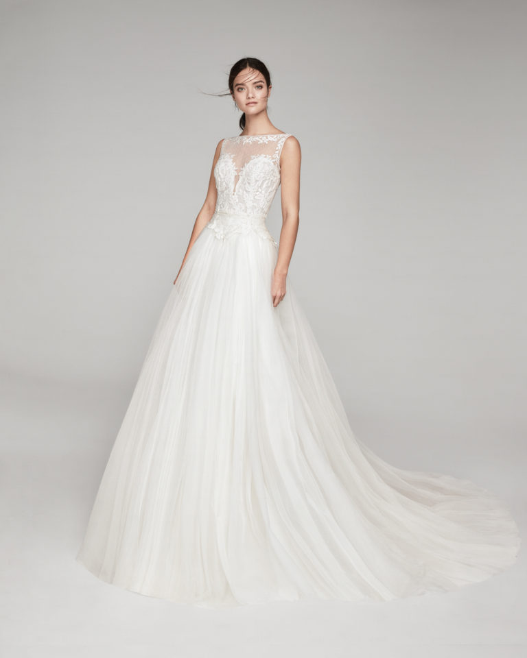 Romantic lace and crepe Georgette wedding dress. With bateau neckline and tulle back. With tulle overskirt. Available in natural. 2019 ALMA_NOVIA Collection.