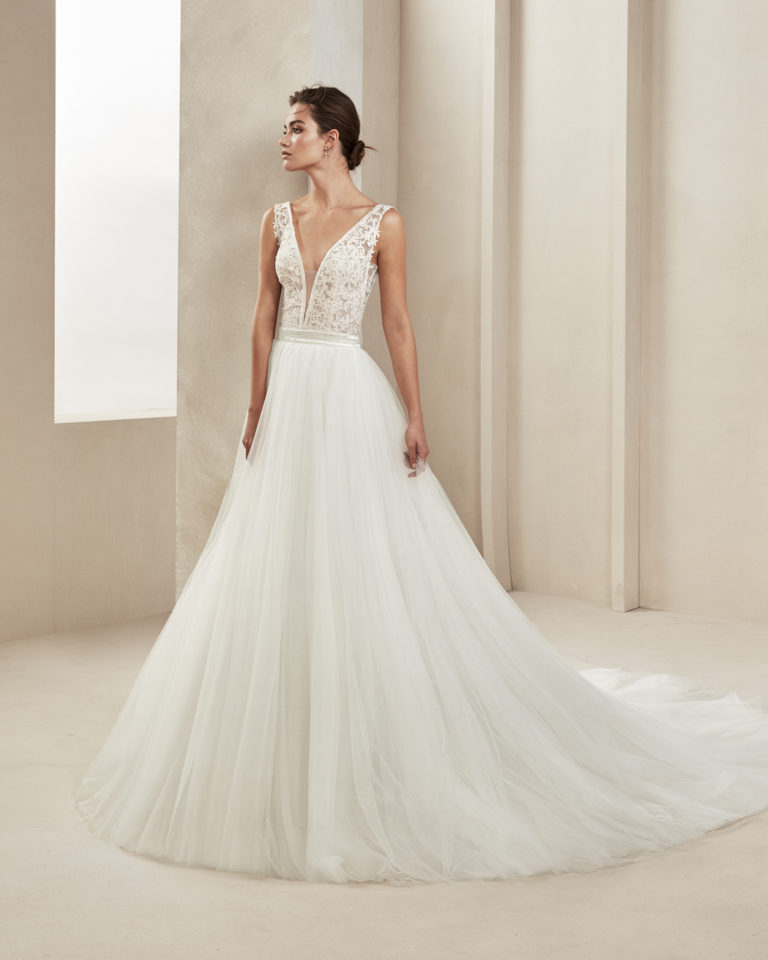 Romantic beaded lace and crepe Georgette wedding dress. With deep-plunge neckline and V-back. With tulle overskirt. Available in natural. 2019 ALMA_NOVIA Collection.