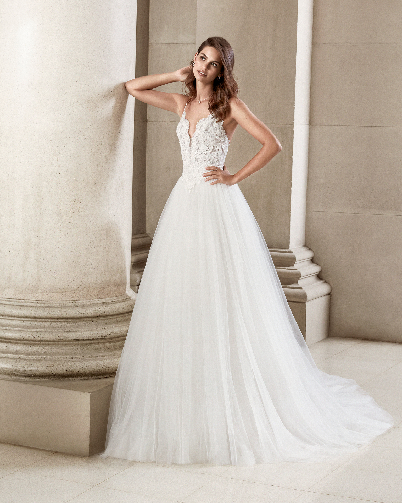 Romantic beaded lace and crepe Georgette wedding dress. With deep-plunge neckline, low back and beaded straps. With tulle overskirt. Available in natural. 2019 ALMA_NOVIA Collection.