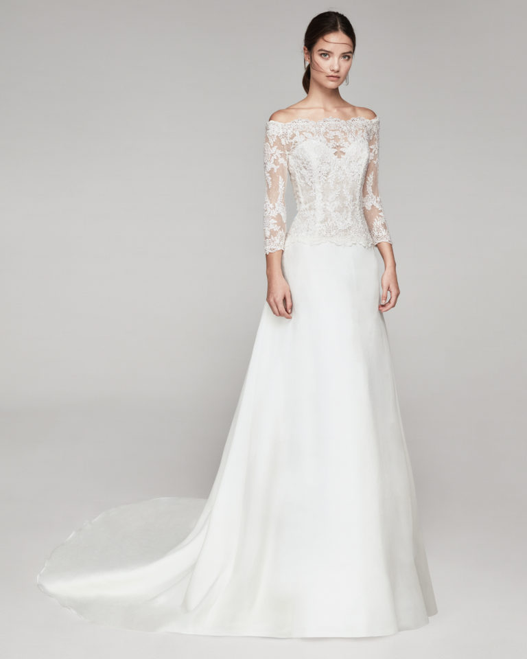 Elegant wedding dress in organza and beaded lace. With off-the-shoulder neckline and three-quarter lace sleeves. Available in natural. 2019 ALMANOVIA Collection.
