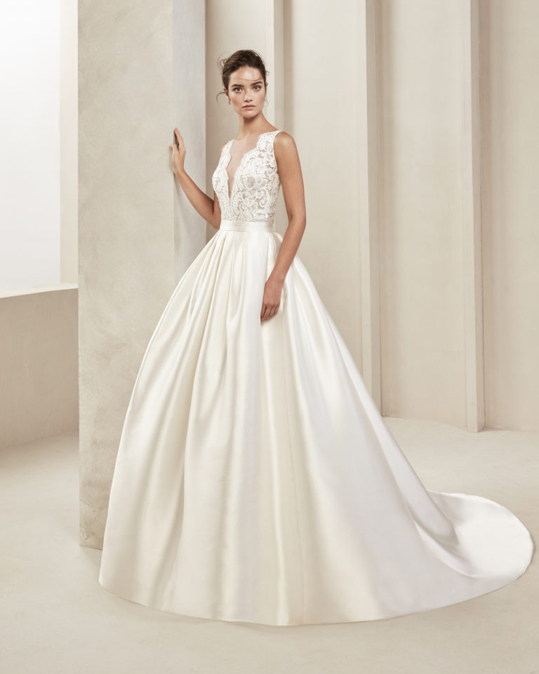Classic beaded lace and crepe Georgette wedding dress. With illusion neckline and low back. With tammy overskirt. Available in natural. 2019 ALMA_NOVIA Collection.