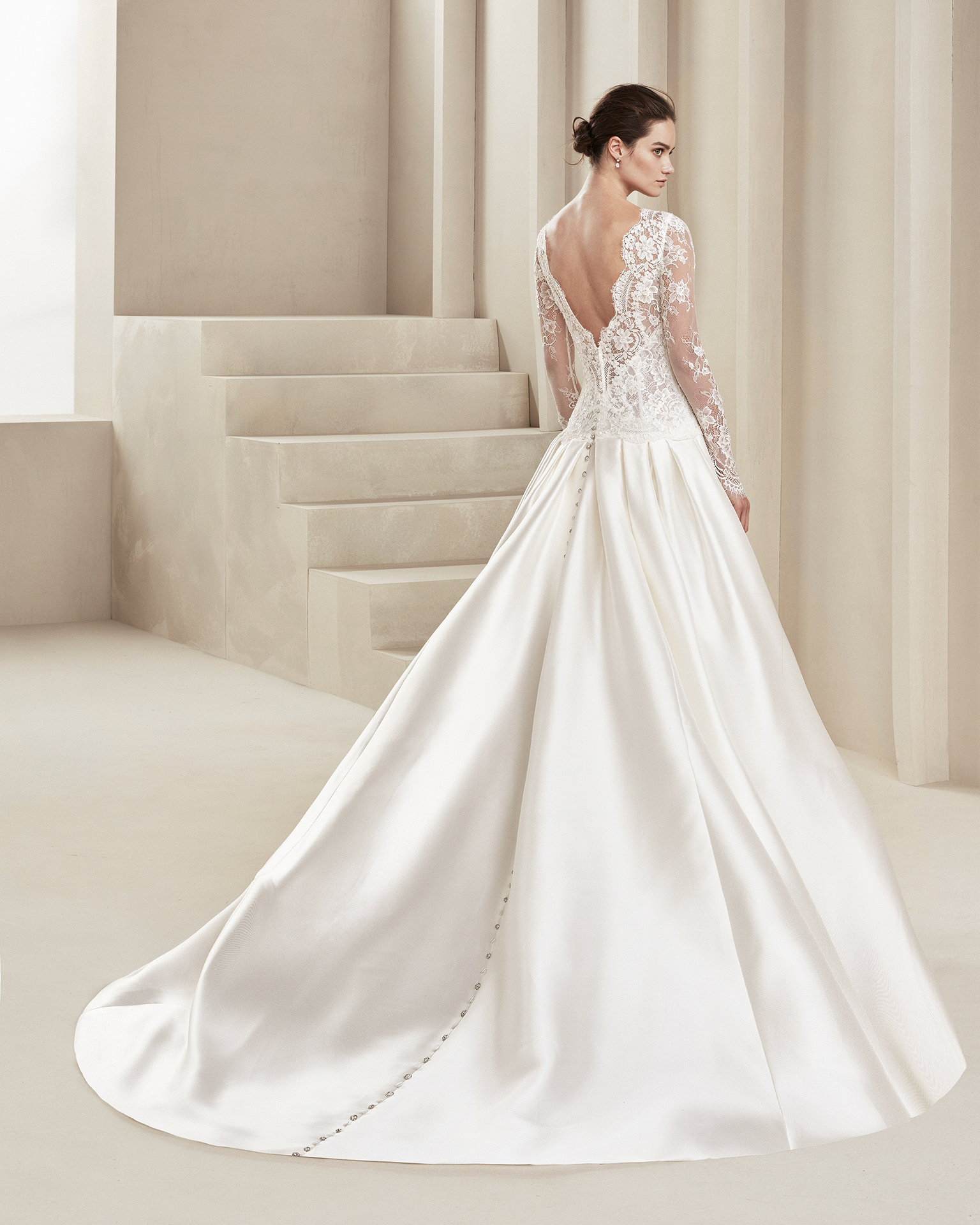 Classic wedding dress in tammy and beaded lace. With deep-plunge neckline, low back and long lace sleeves. With train. Available in natural. 2019 ALMANOVIA Collection.