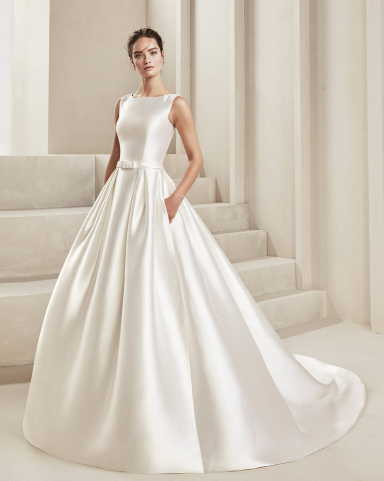 Classic tammy wedding dress. With low V-back and beading. With bow in front at the waist. Available in natural. 2019 ALMA_NOVIA Collection.